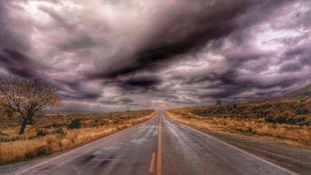 blacktop: A two-lane blacktop heads into a storm. Stock Photo