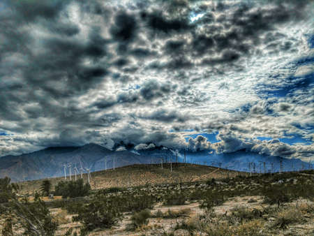 Storm clouds over a desert hill with wind power windmills.