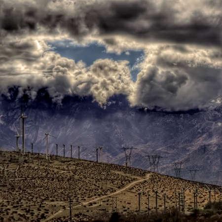Desert storm clouds gather over green power windmills. Stok Fotoğraf