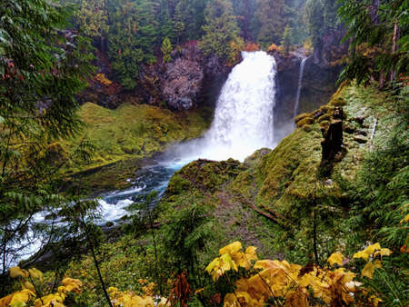 Small lower river waterfall in central Oregon with fall foliage.