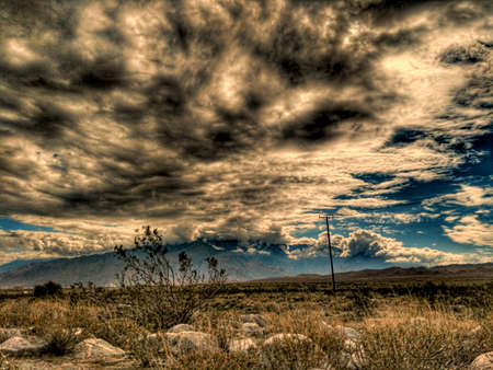 Stormy rain clouds gather over the California Mojave desert near mountains.