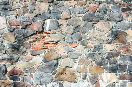 Wall of large natural stones with a piece of brick, natural background.