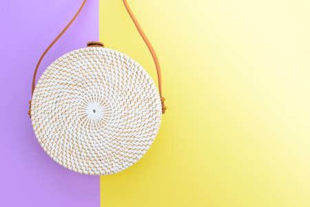 Beautiful round straw handbag on the purple-yellow background. Trendy handbag. Stock fotó