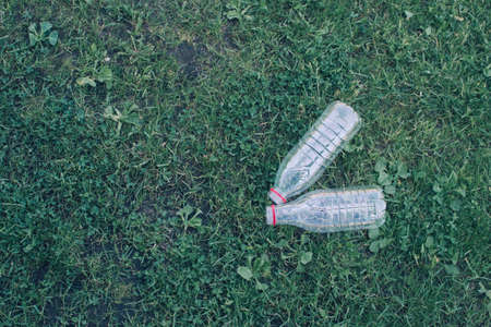 Two used plastic bottles on the grass background. Waste separation concept.