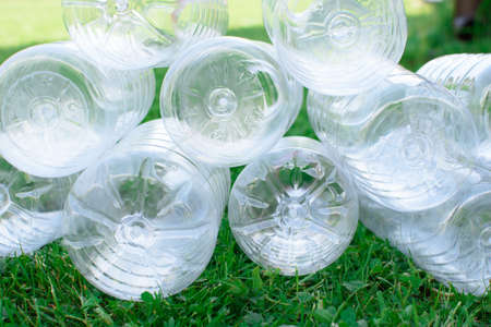 Bottoms of used plastic bottles on the grass, the concept of ecology. Waste separation concept. Stock Photo