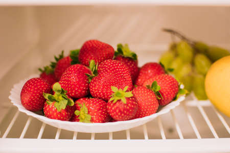 Plate with ripe strawberries is on the shelf of the refrigerator, next to a lemon and grapes. The concept of healthy eating.