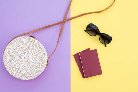 Beautiful round straw handbag and sunglasses with passports  on the yellow-purple background. Trendy handbag.