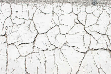 White old cracked paint, cracked by the heat in the sun, on the concrete surface. Great for design and texture background.