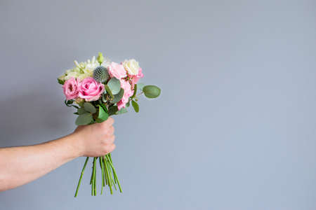 Hand of the man holding a beautiful bouquet of flowers on a gray background. Flowers to gift. Place for text.