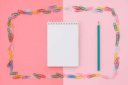 Blank notepad with a green pencil in a frame of colored paper clips on a double background - pink and coral. Concept back to school. 写真素材