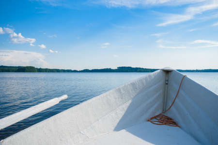 The bow of a white rowing boat on a smooth blue lake, looking at the horizon somewhere in the depths of Finland, a good summer day. Vacation on the lake.