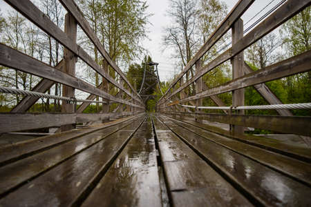 Wooden suspension bridge over the river somewhere in the depths of Finland, gloomy cloudy day. Фото со стока