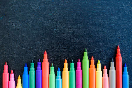 Open multicolored markers closeup on black board background. Place for text.