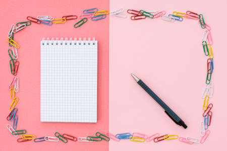 Notebook in cage with a black pen in a frame of colored paper clips on a double background - pink and coral. Concept back to school. 写真素材