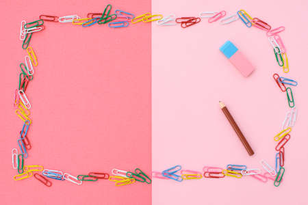 Colored paper clips in the form of a frame, and a pencil with eraser, on a pink-coral background. Concept back to school. Place for text. 写真素材