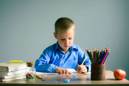 Boy in a blue shirt sitting at the table and draws in a notebook, on the table books, pencils, Apple and other stationery. Boy learning.