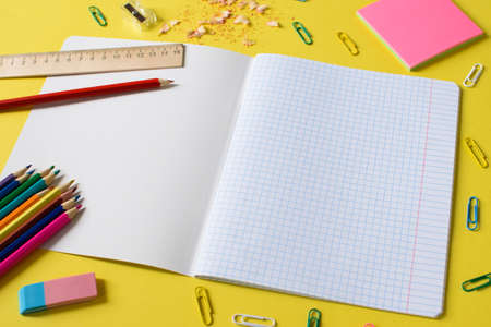 Notebook in a cage with a pencil, eraser, ruler, paper clips and other office supplies on a yellow background. Concept back to school. Place for text. 版權商用圖片
