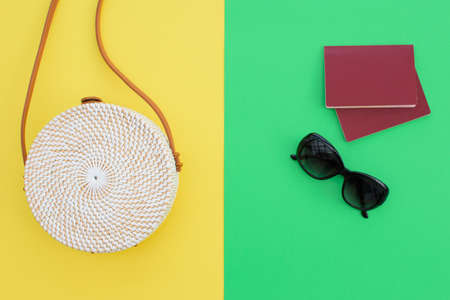 Beautiful round straw handbag and sunglasses with passports  on the yellow-green background. Trendy handbag. Standard-Bild - 129172100