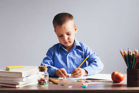 Boy in a blue shirt sitting at the table and draws in a notebook, on the table books, pencils, apple and other stationery. Concept back to school.