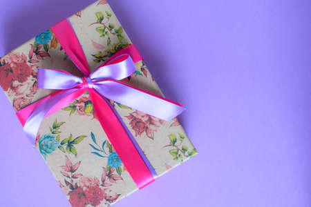 Craft gift box with different beautiful flowers and satin ribbon on the purple background.