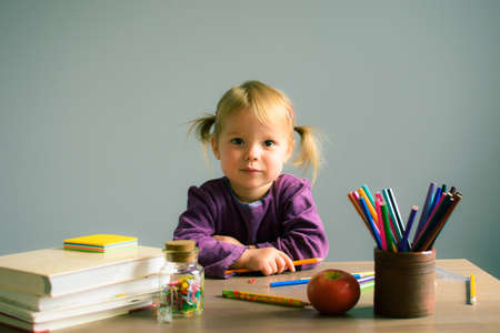 The little girl sitting at the table and draws in a notebook, on the table books, pencils, apple and other stationery. Concept back to school. Zdjęcie Seryjne