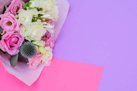 Colorful beautiful bouquet of different fresh flowers on the pink-violet background. Floral arrangement. Close up.