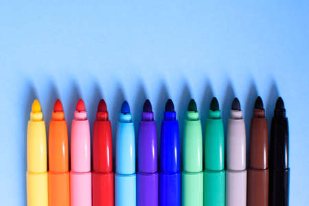 Open multicolored markers closeup on a blue background. Concept back to school.