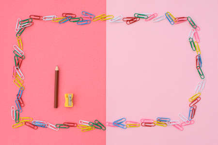 Colored paper clips in the form of a frame, and one pencil and sharpener, on a pink-coral background. Concept back to school. Place for text.