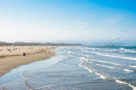 Der größte Strand der Stadt Valencia, der zweitgrößten Stadt Spaniens. Strand, welliges Meer und klarer Himmel.