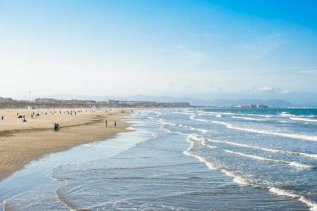 The largest beach in the city of Valencia, the second largest city in Spain. Beach, wavy sea and clear sky.