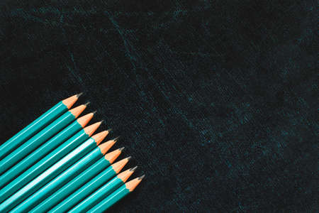 Lots of pencils on black board background with copy space. Back to school concept. Flat lay.