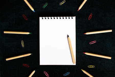 Open notepad and open multicolored pencils on a black board background. Place for text. Concept back to school. Stock fotó