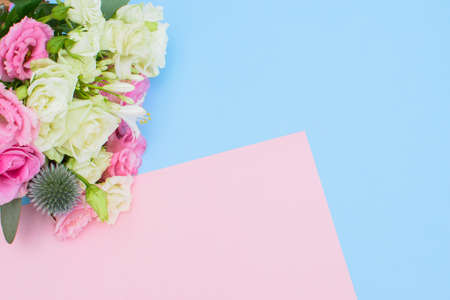 Colorful beautiful bouquet of different fresh flowers on the light blue-pink background. Floral arrangement. Close up.