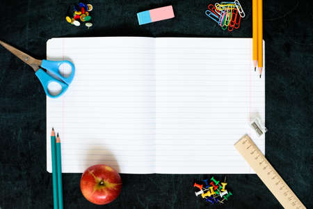 Office and school supplies on black board background with copy space. Back to school concept. Flat lay.