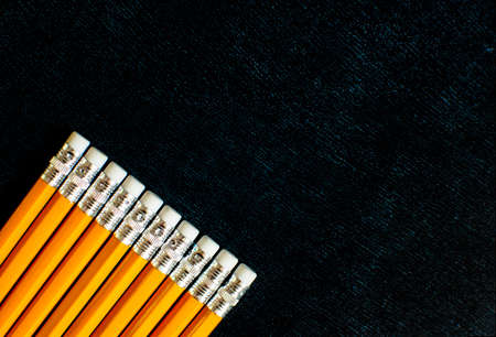Lots of pencils with erasers on pencils on black board background with copy space. Back to school concept. Flat lay.