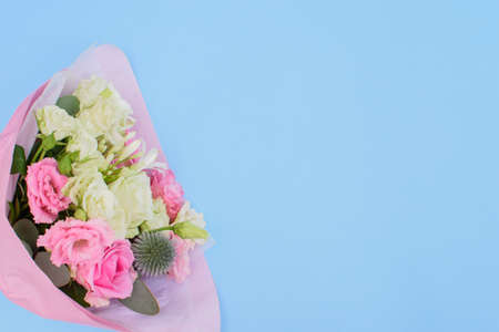 Colorful beautiful bouquet of different fresh flowers on the light blue background. Floral arrangement. Close up.
