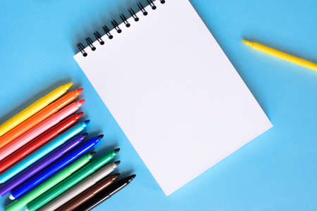 Open notepad and open multicolored markers on the blue background. Place for text. Concept back to school.