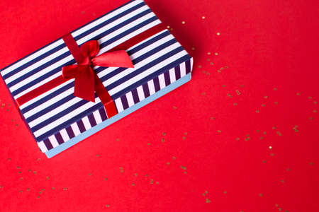 Gift striped box with a red satin bow and with lots of small stars on the red background. Banco de Imagens