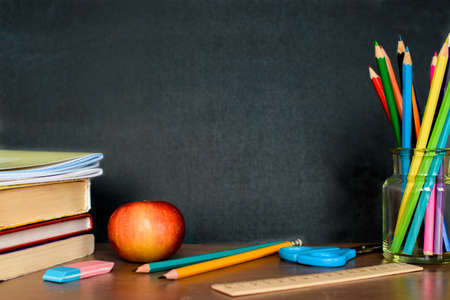 Office and school supplies on black board background with copy space. Back to school concept.