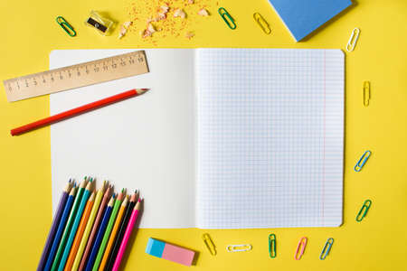 Notebook in a cage with a pencil, eraser, ruler, paper clips and other office supplies on a yellow background. Concept back to school. Place for text. Stock Photo