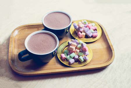 Two cups of cocoa with multicolored marshmallow on a golden saucers. 스톡 콘텐츠