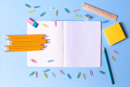 Notebook in a cage with a pencils, eraser, ruler, paper clips and other office supplies on a blue background. Concept back to school. Place for text.