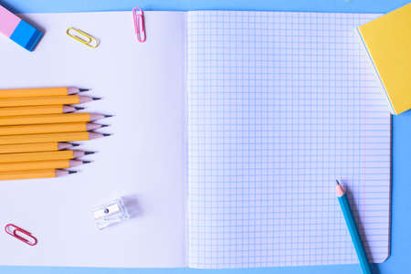 Notebook in a cage with a pencil, eraser, ruler, paper clips and other office supplies on a blue background. Concept back to school. Place for text.
