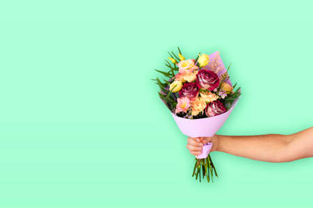 Hand of the man holding a beautiful bouquet of flowers on a green mint background. Flowers to gift. Place for text.