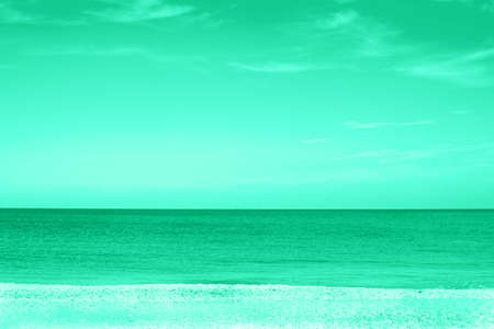 View of the sea and the sky with clouds from the beach in green mint colors. Clear horizon. Great for design and texture background.