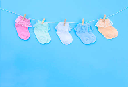 Colorful cute baby socks hanging on the clothesline on blue background. Baby accessories. Flat lay.