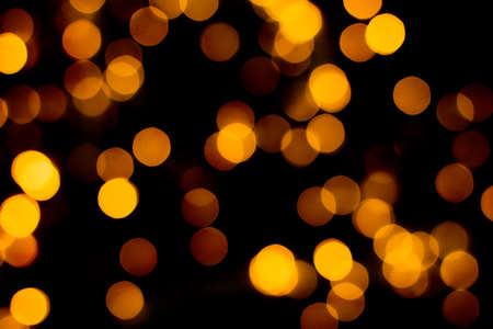 Blurred abstract gold glitter texture, defocused christmas lights on black background. Holiday christmas concept.