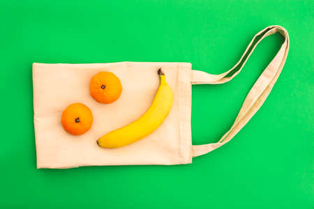Canvas cotton white bag and banana with tangerines on the bright green background. Eco Friendly reusable bag for shopping. Eco and zero waste concept. Banque d'images