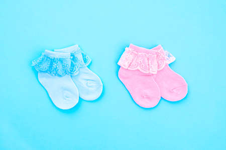 Two pair blue and pink cute baby socks on blue background. Baby accessories. Flat lay.