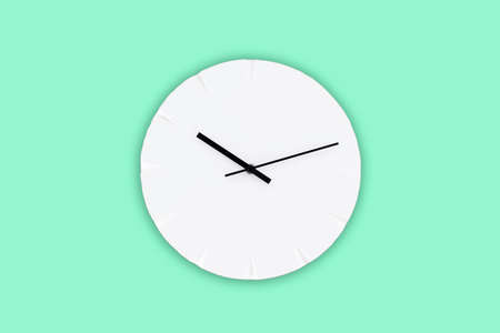 White wall clock with black clock hands hanging on the green mint wall. Minimalist flat lay image.